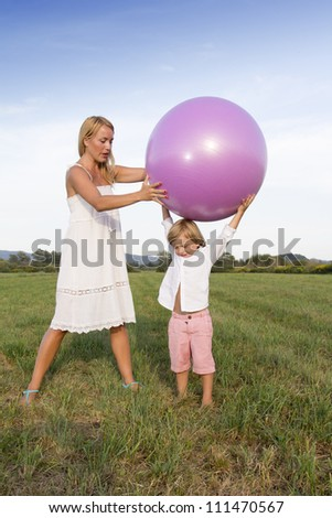 Cute young woman and her son playing outdoors with fit ball