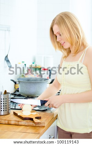 cute young woman cutting onion at kitchen