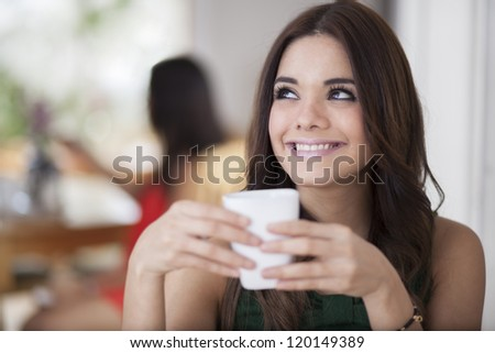 Cute young woman enjoying a cup of coffee in a restaurant and looking towards copy space