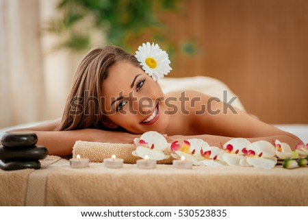 Cute young woman enjoying during a skin care treatment at a spa.