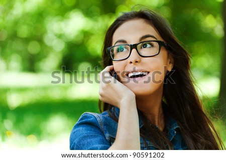 cute young woman glasses park talking phone smiling - stock photo