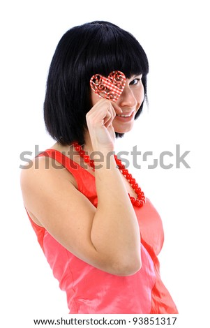 Cute young woman holds a heart symbol to her face