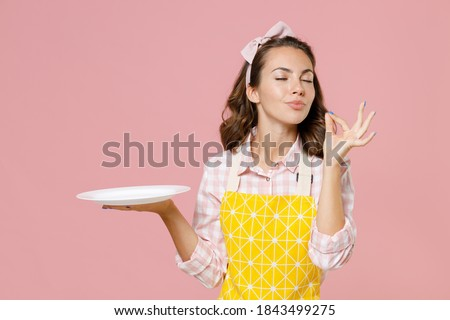 Cute young woman housewife in yellow apron hold empty plate making okay taste delight sign keeping eyes closed doing housework isolated on pastel pink background studio portrait. Housekeeping concept