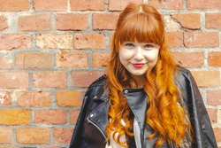 Cute young woman in a black leather jacket with curly red hair and bangs smiles against a brick wall with copy space