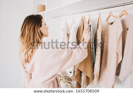 Cute young woman in bathrobe standing in front of hanger rack and trying to choose outfit dressing for work or walk. Selection of a wardrobe, stylist, shopping. Foto stock ©