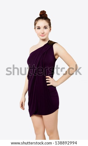 Cute young woman in plum dress on white background