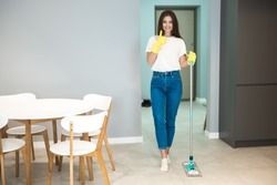 cute young woman in yellow gloves doing cleaning washing kitchen floor showing like sign