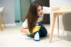 cute young woman in yellow gloves with detergent spray in her hand wiping dust off from the kitchen chair with a rag thoroughly