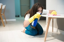 cute young woman in yellow gloves with detergent spray in her hand wiping dust off stain from the kitchen chair with a rag thoroughly
