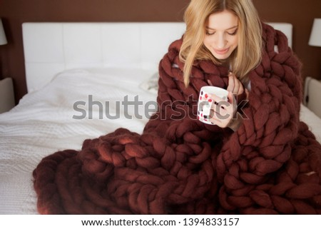cute young woman is sitting on the bed wrapped in a big and fluffy brown plaid. Beautiful girl in a cozy blanket with a Cup of tea. Warmth and comfort of home, concept Stock photo ©