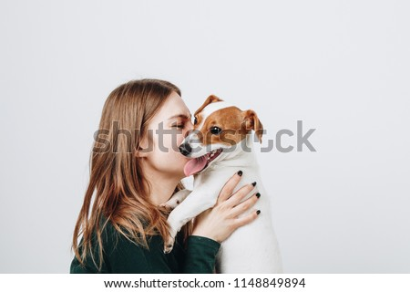 Cute young woman kisses and hugs her puppy  jack russell terrier dog. Love between owner and dog. Isolated on white background. Studio portrait.