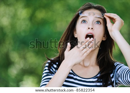 cute young woman looking up surprised raised glasses covers mouth his hand