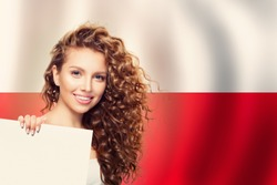 Cute young woman showing white paper on the Poland flag background. Travel and learn polish language concept