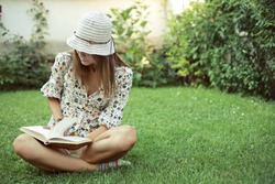 Cute young woman sitting on the grass and reading the book