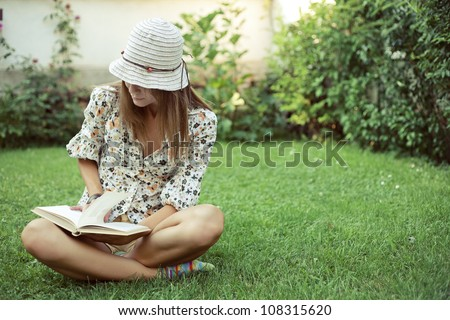 Cute young woman sitting on the grass and reading the book #108315620