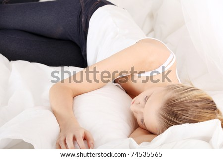 Cute young woman sleeping on the bed in casual clothes