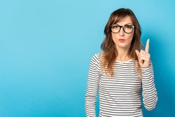 Cute young woman with glasses and a striped sweater, a serious face points a finger upwards on an isolated blue background. Emotional face. The concept is something important, pay your attention