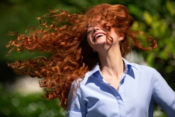 Cute young woman with streaming hair and a lovely sense of humour laughing at the camera