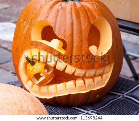 Cuted Halloween pumpkin eating small pumpkin
