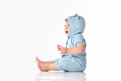 Cutie child wearing funny blue costume, sitting on the floor, showing tongue, looking at camera. Full-length portrait of a toddler. Isolated studio shot on white background with copy space