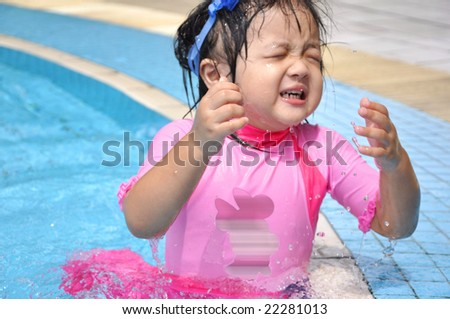cutie girl playing at the swimming pool