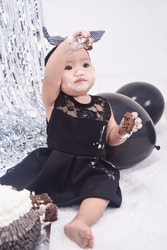 Cutie girl who is having her first birthday, on black lace dress and headband, with cake and balloons. Birthday party concept.