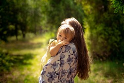 cutie little baby girl in yellos dress hugs her mother at the green garden