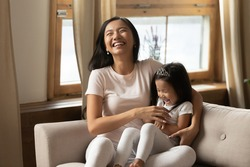 Cutie little daughter seated on mommy lap on couch laughing enjoy funny active time with loving parent. Asian excited young mother tickling adorable preschooler kid girl feels happy be mother concept