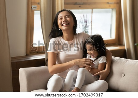 Cutie little daughter seated on mommy lap on couch laughing enjoy funny active time with loving parent. Asian excited young mother tickling adorable preschooler kid girl feels happy be mother concept stock photo