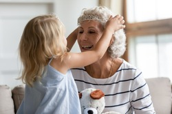 Cutie small granddaughter imagines herself like princess play with elderly grandmother puts on her head crown appointing her a queen. Funny activity at home, family time together amusing games concept