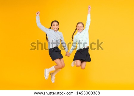 Cuties in mid air. Active children jumping high on yellow background. Happy girls enjoying active lifestyle. School friends having fun activities together. Active generation. Active and energetic.
