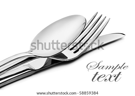 Cutlery - a spoon, fork and knife stacked up on a white background with space for text (focus on the fork)