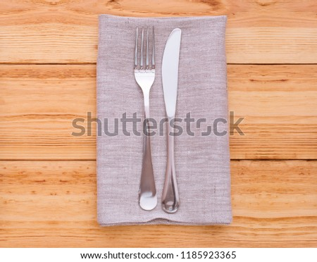 cutlery and napkin on wooden table closeup. Mock up napkins for design. Napkins top view square.