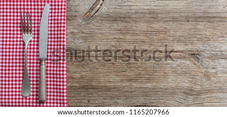 Cutlery and red checkered picnic tablecloth on wooden table, top view, copy space Foto stock ©