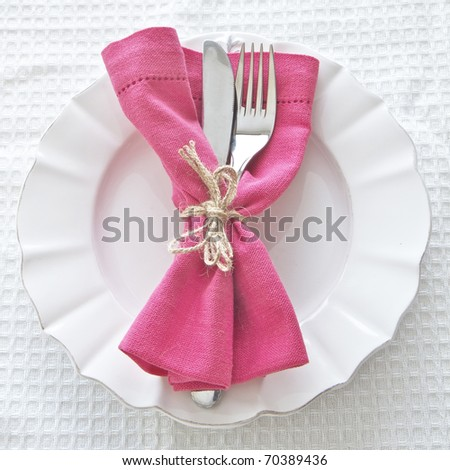 Cutlery on white plate with pink napkin