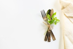 Cutlery with natural linen napkin on white table background.