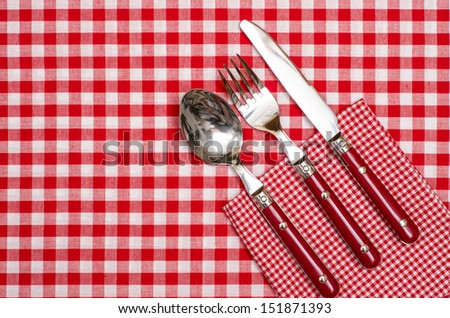 Cutlery with red knife, fork and spoon on red checked napkin and table cloth