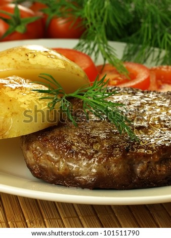 Cutlet, potatoes and tomatoes with green dill in a background