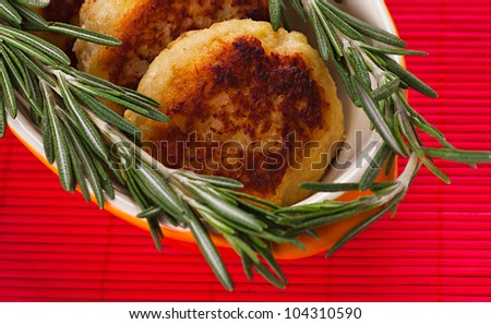Cutlets with fresh rosemary on plate located on red bamboo napkin.