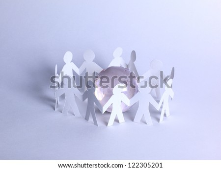 Cutout paper people standing around globe holding hands.