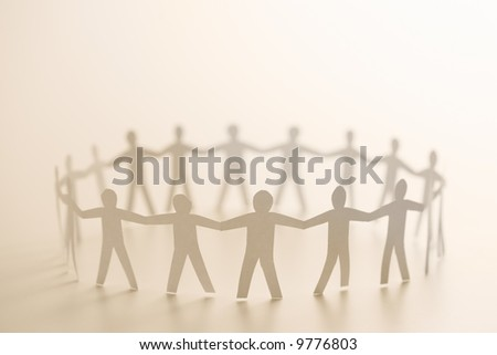 Cutout paper people standing in circle holding hands.