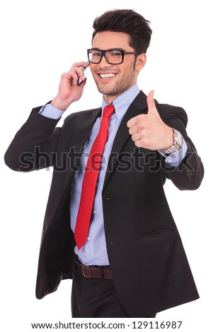 cutout picture of a young business man showing thumbs up sign and speaking at the phone while smiling to the camera on a white background