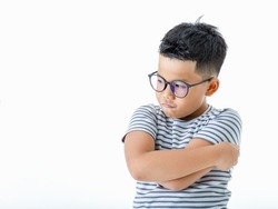 Cutout portrait of lovely young Asian healthy boy wearing glasses and casual horizontal striped shirt standing with arms crossed looks serious, confident, and determined