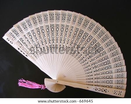 Cutout wooden oriental fan on black