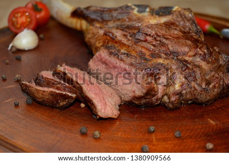 cuts of beef angus beef, roasted on the grill on top of a wooden board with red complements.