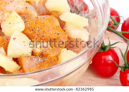 Cutted chicken breast fillet with pineapple in glass bowl, closeup