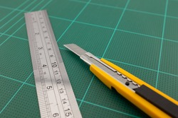 Cutter and steel ruler on cutting pads