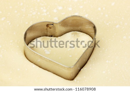 Cutter in the shape of a heart on the rolled out dough close-up - stock photo