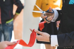 Cutting a red ribbon with scissors