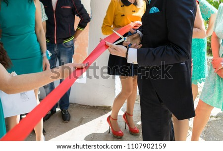 Cutting a red ribbon with scissors, inaugurated ribbon